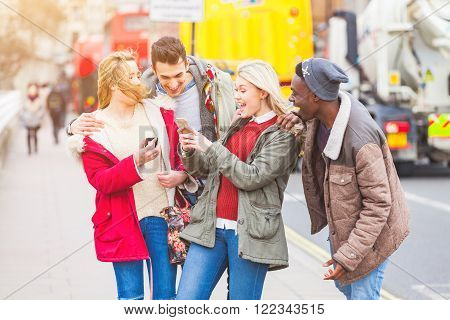 Group of young friends having fun in London. Mixed races people laughing and enjoying their time looking at a smart phone. Very candid and natural image with real expressions of happiness.