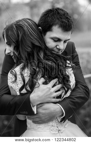 Cheerful Romantic Newlywed Couple Hugging In Park Alley Closeup B&w