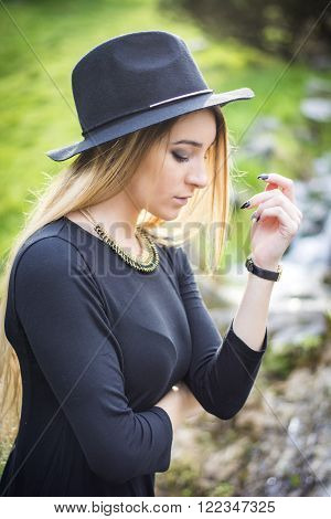 Pretty blonde young woman outdoor in city park, wearing short black dress and fedora hat