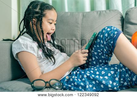 Cute little girl dreadlocks hair style playing with computer at home laying on sofa