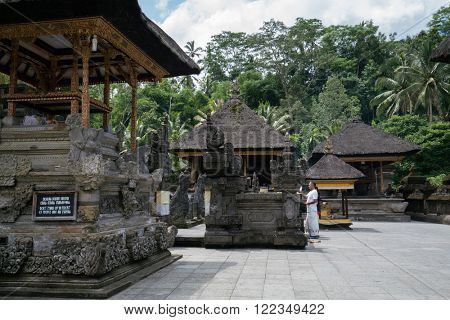 UBUD, BALI - MARCH 14, 2016: A Balinese Hindu priest performs prayers at the altar inside the Pura Tirta Empul (temple), Bali.  Hinduism is the religion of the original Balinese inhabitants.