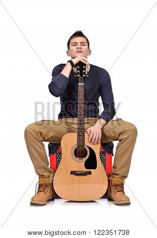 man playing on acoustic guitar sitting on combo amp