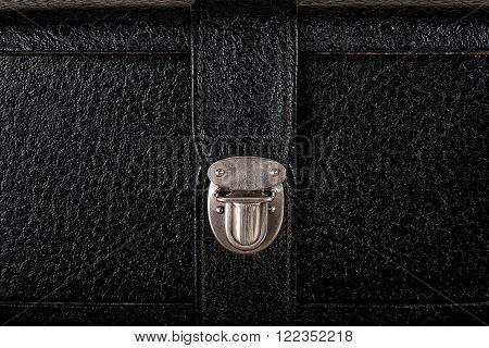 Metal buckle on vintage case of textured black leather closeup.