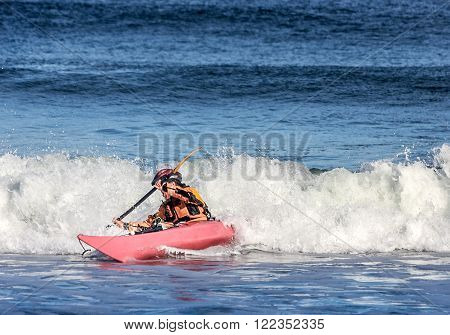 Kayaker fighting the crest of a wave in rough sea of Nova Scotia coast Canada