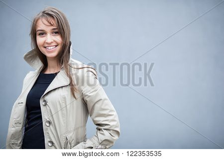Elegant young woman wearing a trench coat and posing in front of a grey wall (shallow DOF; color toned image)