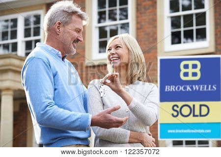 Mature Couple With Keys To New Home