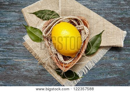 Fresh lemon with a linen rope in the wooden plate
