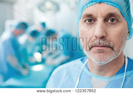Experienced mature surgeon is looking forward seriously. He is standing in blue uniform. His surgical team is doing the operation on background