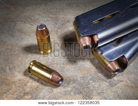 Handgun cartridges with hollow point bullets and magazines nearby