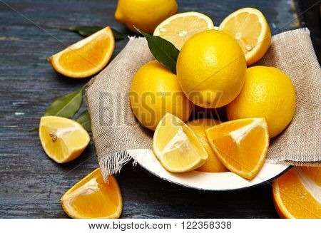 Fresh lemons and oranges in an old plate