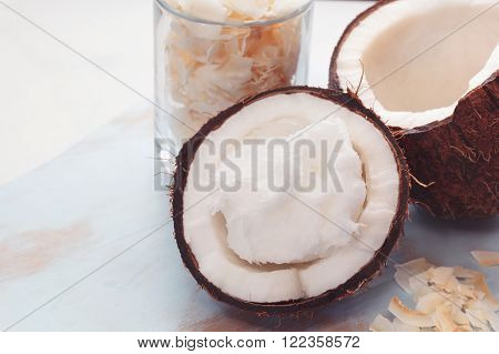 Fresh coconut with coconut oil , grated and coconut  coconut  flakes over rustic background. Macro selective focus, vintage toned image