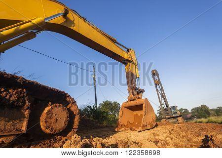 Earthworks Excavator bin and mobile crane industrial earthworks construction on site.
