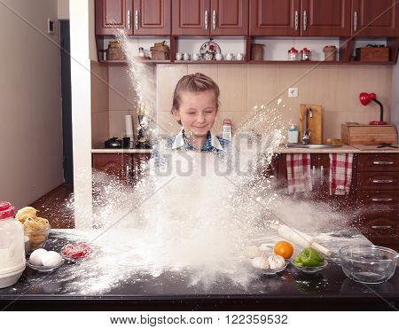 little girl is helping to bake in a messy kitchen