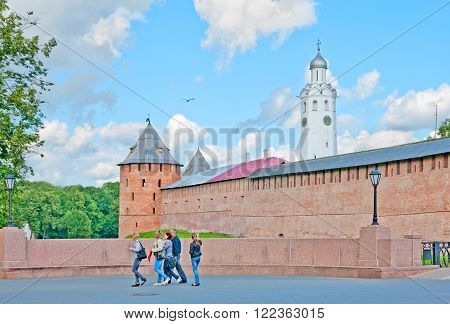 VELIKY NOVGOROD, RUSSIA - JULY 17, 2016. People on the bridge over the moat. On the background is The Kremlin Wall with Mitropolichya Tower and The Clock Tower