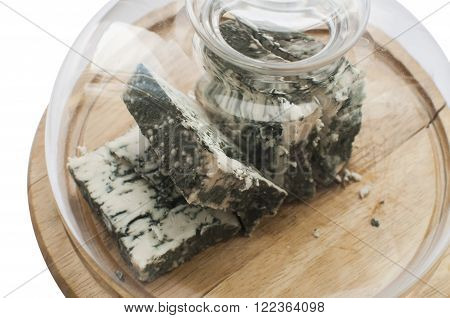 Sliced lump of moldy white cheese under glass lid on wooden tray isolated on white background