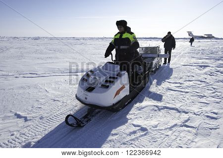 Chukotka Russia - April 28 2011: A member of the polar station in the North Arctic Ocean operates a snowmobile on a temporary runway drifting ice floe. Bright sunny day the vast expanse of snow.