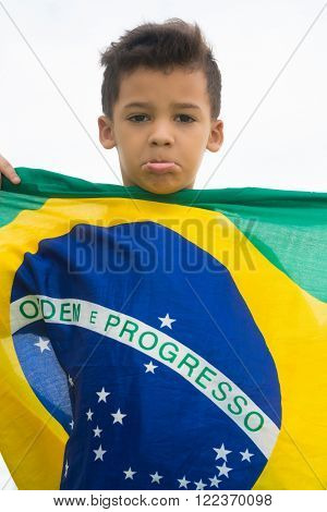 Patriot / Sad child holding the Brazil's flag