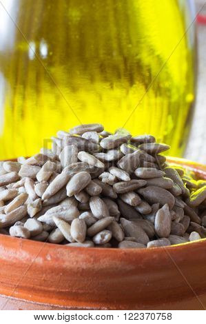 Organic and Raw Sunflower Seeds in a Bowl and Bottle of Oil.