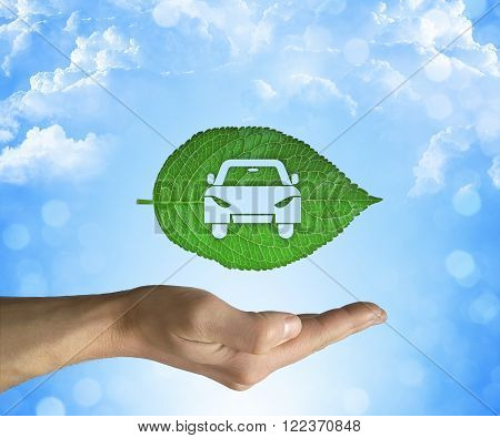 Opened hand holding a green leaf with a car icon inside on a blue sky background. Eco car concept