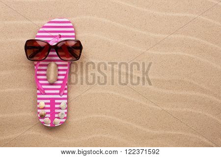 Concept of a woman's face flip-flops and sunglasses on wavy in sand