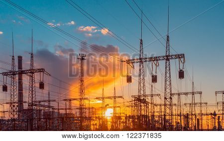 distribution electric substation with power lines and transformers at sunset clouds