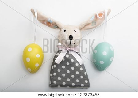 Easter Bunny toy with dyed colorful dotted eggs on long ears, with a bow in a gray polka-dot dress on isolated background