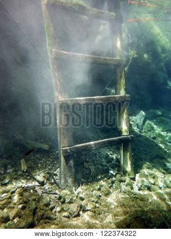 An underwater wooden stairs in the natural limestone Gran Cenote near the city of Tulum in the Mexican province Yucatán.