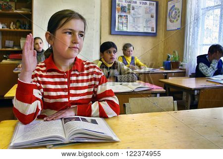 Podol village Tver region Russia - May 7 2006: Rural girl schoolgirl Tanya 11 years old raises his hand sitting at the desk in the classroom.