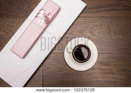 Topview of wooden desktop with girly gift case and coffee cup