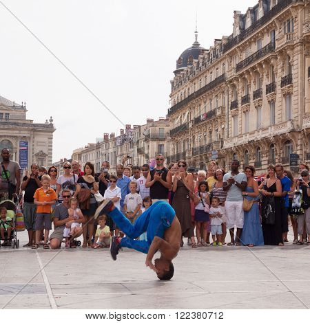 Montpellier, France - July 12: Street performer breakdancing on main square in front of the random crowd on July 12, 2011 in Montpellier, France.