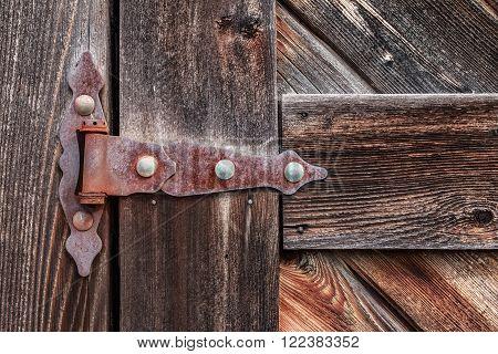 Old rusty hinge on wooden weathered door.