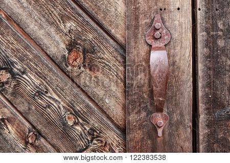 Old rusty metal handle on wooden weathered door