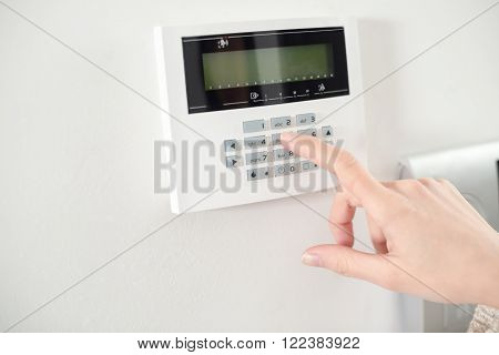 Close up on brunette woman's hand entering code on keypad of home security alarm. Video intercom next to alarm keypad.