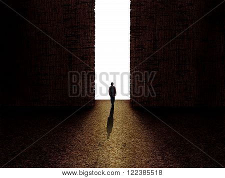 Man walking towards the light from darkness with white background