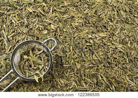 A tea strainer and loose leaf green tea leaves filling the frame