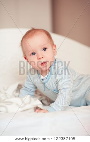 Cute baby boy wake up in bed in room. Wearing pajamas. Looking away. Good morning.