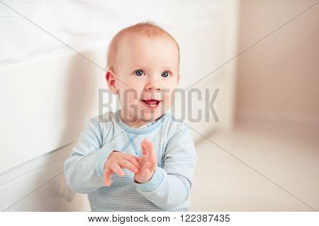 Smiling baby boy 1 year old sitting on floor in room. Happiness. Cheerful. Childhood.