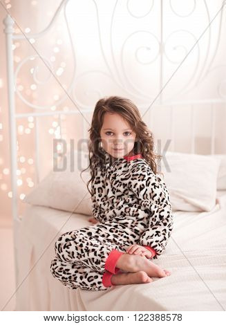 Cute kid girl 4-5 year old sitting in bed over lights in room. Looking at camera. Childhood. Good morning.