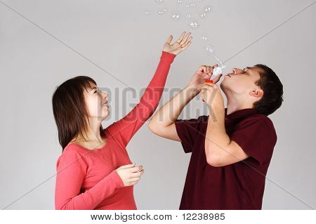 Young Man Blowing Out Soap Bubbles, Girl In Red Shirt Smiling And Catching It