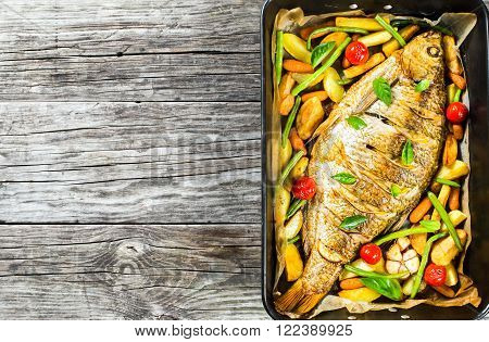 whole fish baked in a baking dish top view