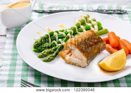 delicious hake baked in oven and served with asparagus a lemon slice baby carrots and the hot hollandaise sauce on the white platter on the table-napkin
