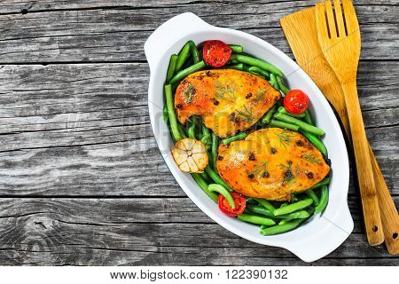 Chicken breast with green bean garlic and tomatoes in the baking dish decorated with fennel leaves view from above