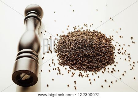 pepper mill and peppercorns heap, white background