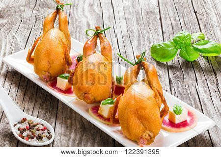 smoked quail on a rectangular dish close-up