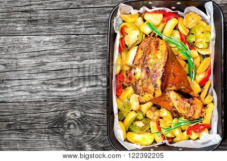 roast pork knuckle with potatoes pepper garlic spices top view