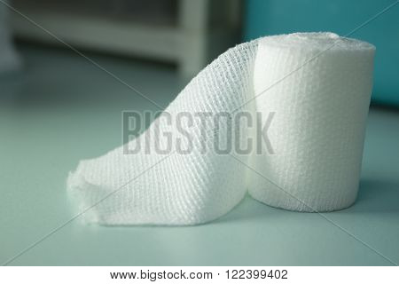 Gauze roll on operating table. White color.
