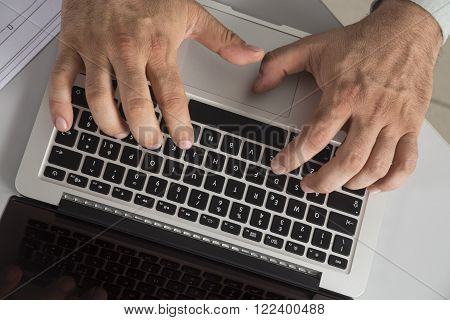 Two hands typing on a black keyboard 2