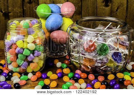 assorted jars of gumdrops lollipops jelly beans colored eggs on wood background