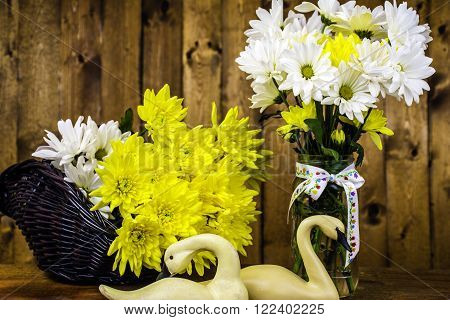 basket and mason jar with flower bouquets and carved swans on wood background