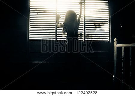 Ghost girl in haunted house,Mysterious girl in black dress standing in abandon house holding hand on the window